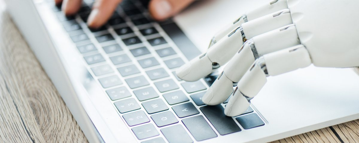 Robot and human hand on laptop keyboard